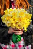 figure girl with bouquet of daffodils in his hands