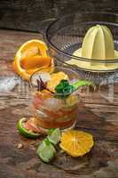 fresh juice of tropical citrus fruits on wooden background