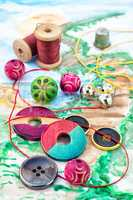 Threads and embellishments on a colorful background