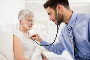 Home nurse listening to chest of patient with stethoscope