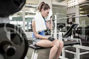 Tired brunette on bench wiping sweat with towel