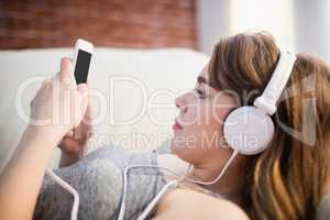 Pretty woman lying on the couch using her phone and listening mu