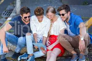 Hip friends looking at tablet and sitting on sidewalk