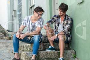 Hip men sitting on steps and looking at smartphone