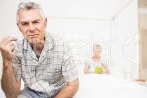 Suffering senior man touching his forehead