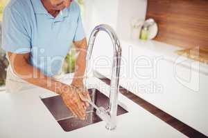 Mid section of senior man washing hands