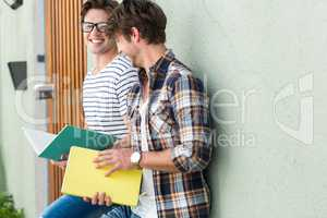 Hip men leaning against wall and holding notebooks