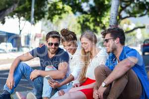 Hip friends looking at smartphone and sitting on sidewalk