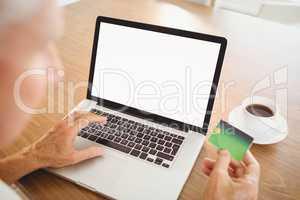 Elderly man spending money on internet