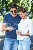 Hip couple looking at smartphone