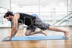 Muscular man doing push up on mat