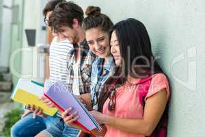 Hip friends leaning against wall and reading notebooks