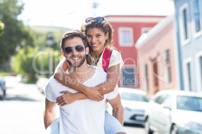 Hip man giving piggy back to his girlfriendq
