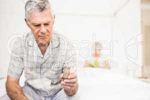 Suffering senior man taking pills