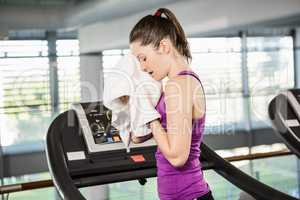 Tired brunette on treadmill wiping sweat with towel