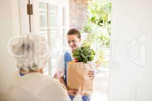 Nice nurse bringing vegetables to old patient