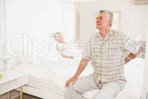 Suffering senior man holding his back