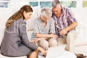 Smiling businesswoman showing laptop monitor to senior couple