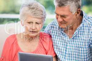 Doubtful senior couple using tablet
