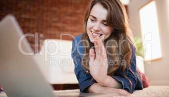 Pretty smiling woman lying on the floor waving at laptop