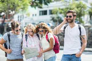 Hip man on phone call and friends checking map