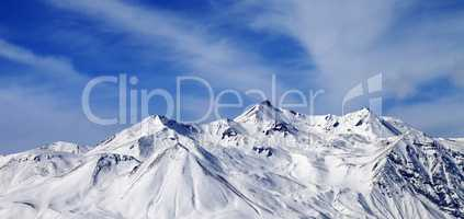 Panoramic view on winter snowy mountains in windy day