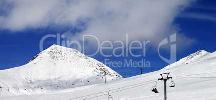 Panoramic view on chair-lift and ski slope at sun day