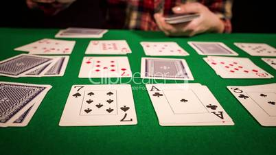 Close up of female hands holding cards and playing solitaire
