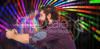Composite image of side view of happy hipster playing video game