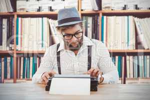 Composite image of hipster wearing eye glasses and hat working o