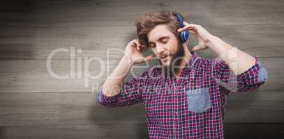 Composite image of hipster wearing headphones