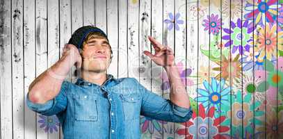 Composite image of cheerful hipster listening to music