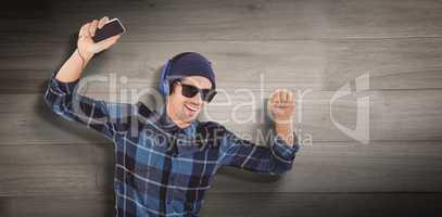 Composite image of portrait of happy hipster wearing headphones