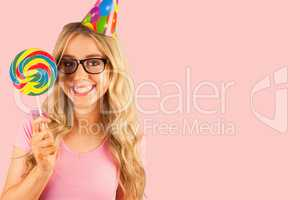 Composite image of portrait of a hipster with a party hat holdin