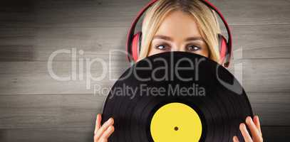 Composite image of portrait of a beautiful woman holding a vinyl