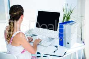 pregnant business woman typing on her computer