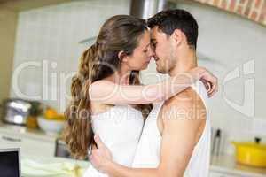 Young couple cuddling in kitchen