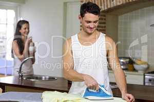 Man ironing a shirt in kitchen