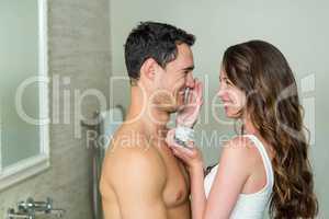 Woman applying moisturizer on man's face