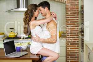 Young couple cuddling on kitchen worktop