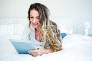 woman lying on her bed browsing on her tablet
