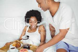 Handsome man bringing breakfast to his girlfriend