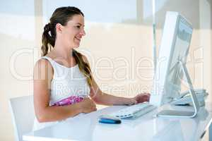 smiling pregnant business woman on her computer