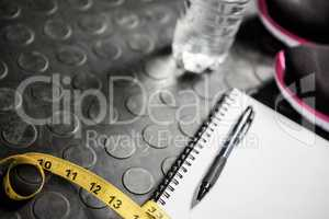 Notepad, measuring tape, shoes and bottle