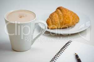 Notebook with pen and coffee by food
