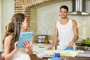 Man talking to woman while ironing a shirt