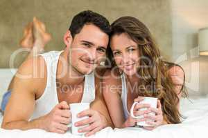 Young couple having cup of coffee on bed