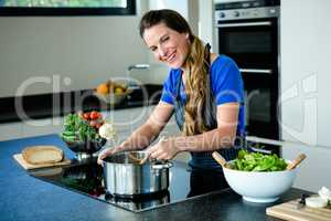 smiling woman cooking on the stove top