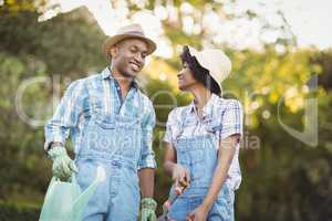 Smiling couple holding watering can and gardening shears