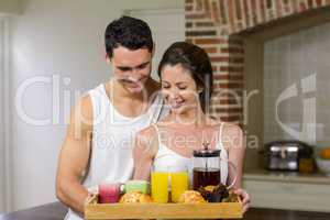 Happy couple carrying breakfast tray in kitchen